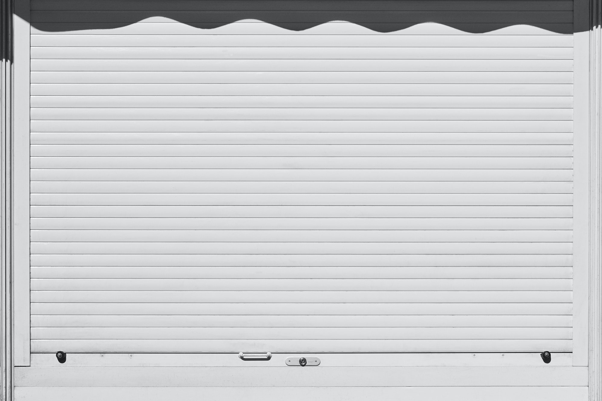 Closed and locked white rolling shutter. Security background. Horizontal